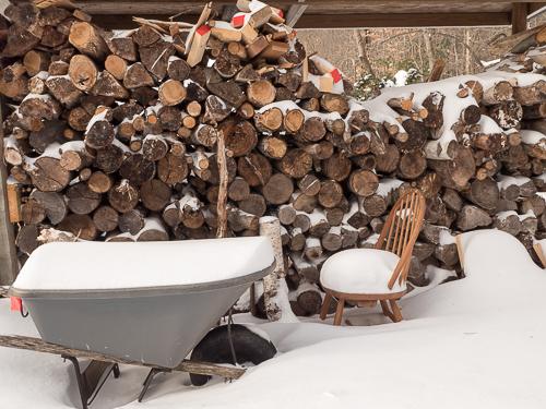 woodpile, wheelbarrow and chair full of snow